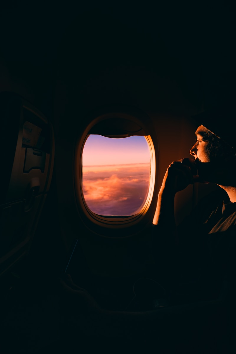 man in black jacket sitting on car seat looking at the window during sunset